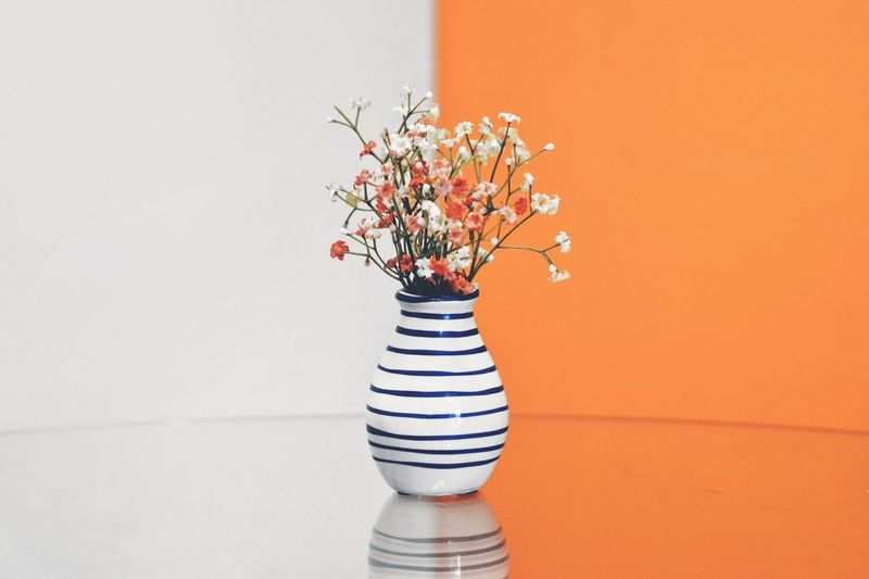 Flower vase against white and orange wall on table