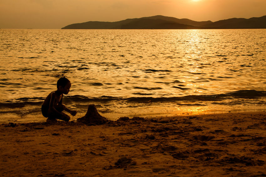 silhouette of people at the beach,The beauty of natural light at sunset. Sunset Water Sea Real People Sky Beauty In Nature Lifestyles Scenics - Nature Beach Leisure Activity Tranquility Sitting Tranquil Scene One Person Mountain Land Nature Idyllic Orange Color Outdoors Silhouette Happiness Happy People Holiday Relaxing Children Women Man Romantic Orange Clouds And Sky Love Family Summer Sunrise Boy Freshair Freedom Fun