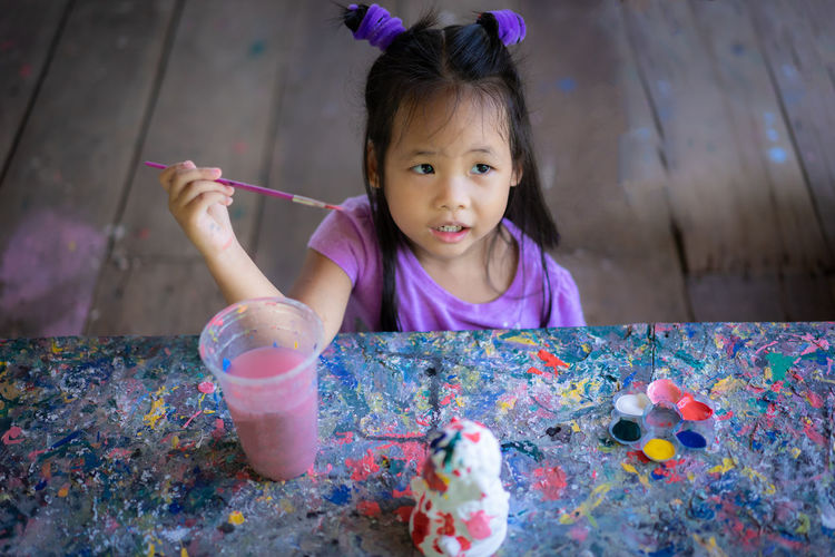 Cute girl holding paintbrush while sitting at messy table