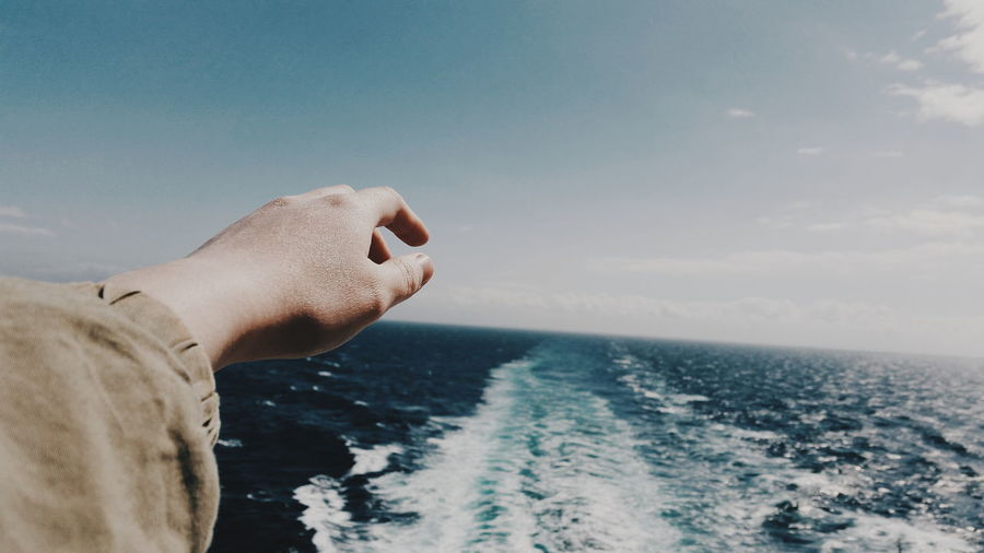 Cropped hand of person gesturing over sea against sky