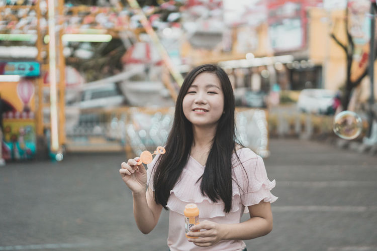 Portrait of young woman holding bubble wand at amusement park