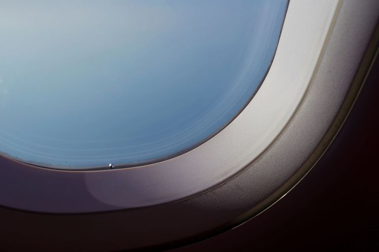 Close-up of airplane wing against blue sky
