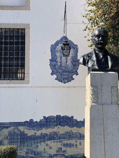 Statue in front of tile work on wall with hanging lamp in Lisbon, Portugal Lisbon Portugal Representation Human Representation Art And Craft Sculpture Statue Male Likeness Architecture Built Structure Creativity Building Exterior No People Day Building Spirituality Religion Nature Craft Low Angle View Outdoors Belief