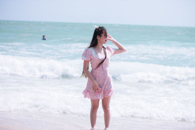 Full length of woman standing on beach against sea
