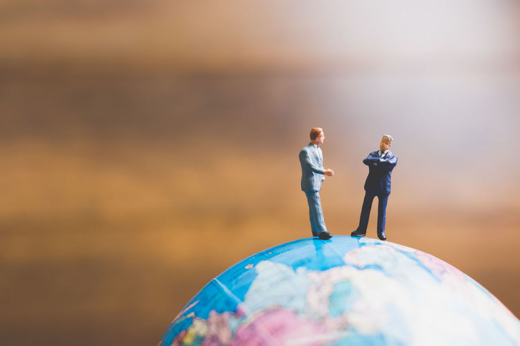 Close-up of entrepreneur figurines on globe