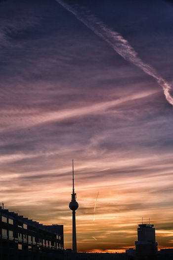 Communications tower in city at sunset