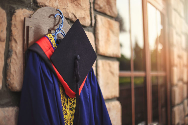 Graduation gown with mortarboard hanging on wall