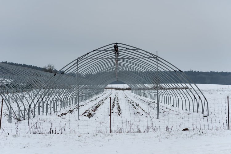 Fence on snow covered field against sky