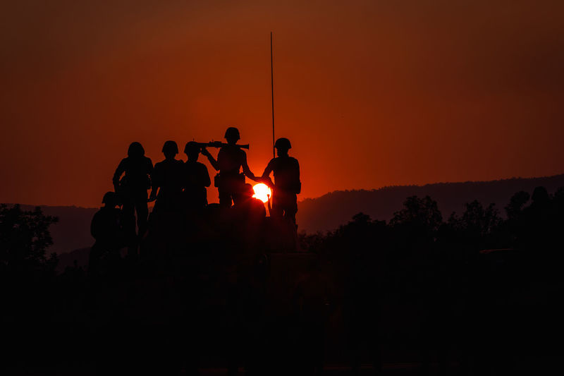 Activity Beauty In Nature Copy Space Group Of People Land Lifestyles Medium Group Of People Men Nature Orange Color Outdoors People Real People Silhouette Sky Soldiers Uniform Standing Sunset Team Work