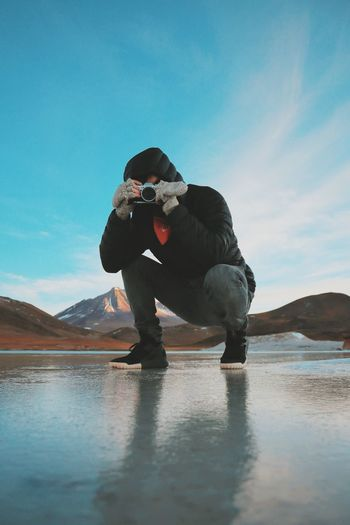 Man Photographing Through Camera While Crouching On Frozen Lake Against Mountains