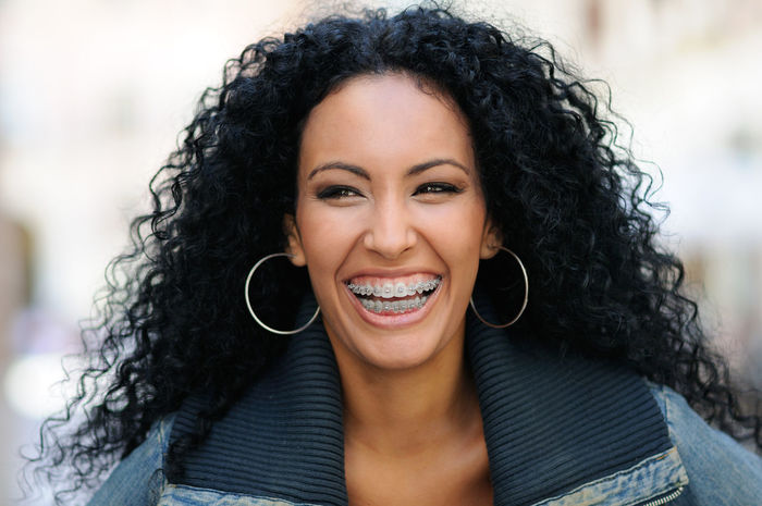Portrait of a young black woman laughing with braces Brackets Laughing Adult Beautiful People Beautiful Woman Beauty Black Hair Cheerful Close-up Confidence  Curly Hair Day Focus On Foreground Happiness Headshot Laugh Long Hair One Person One Woman Only Only Women Outdoors Portrait Real People Smiling Women