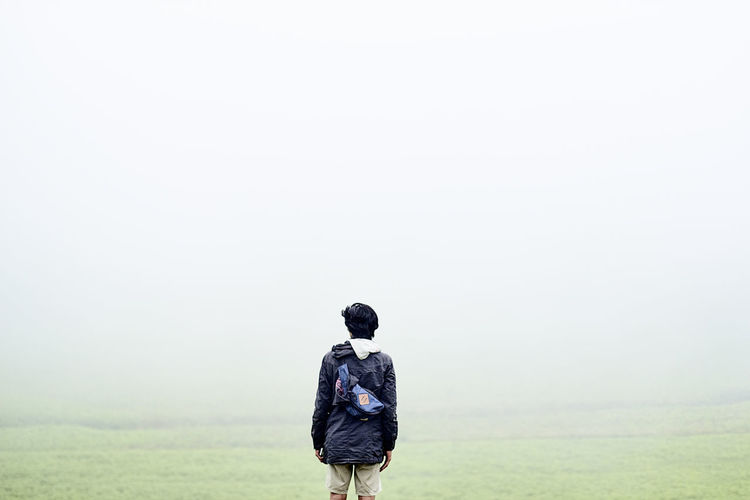 Rear View Of Man Standing On Field Against Sky In Foggy Weather