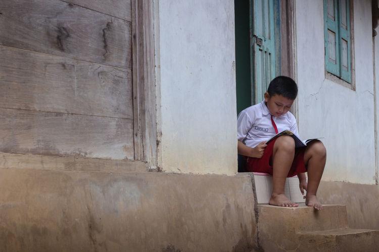 Boy reading book at doorway