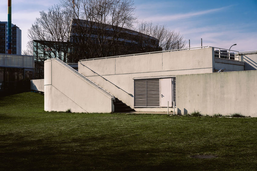 Bauhaus Archives Bauhaus Bauhaus Building Bauhaus Museum Bauhaus Architecture Bauhaus Style Architecture Bare Tree Building Building Exterior Built Structure Cloud - Sky Day Exterior Factory Field Grass Green Color Industry Nature No People Outdoors Plant Sky Sport Tree