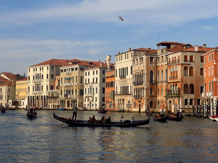Boats in venice canal along buildings
