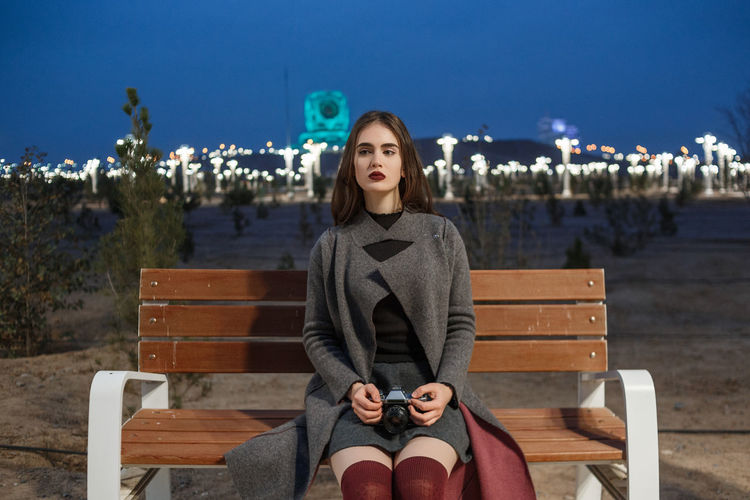 Young woman sitting on bench in park against sky