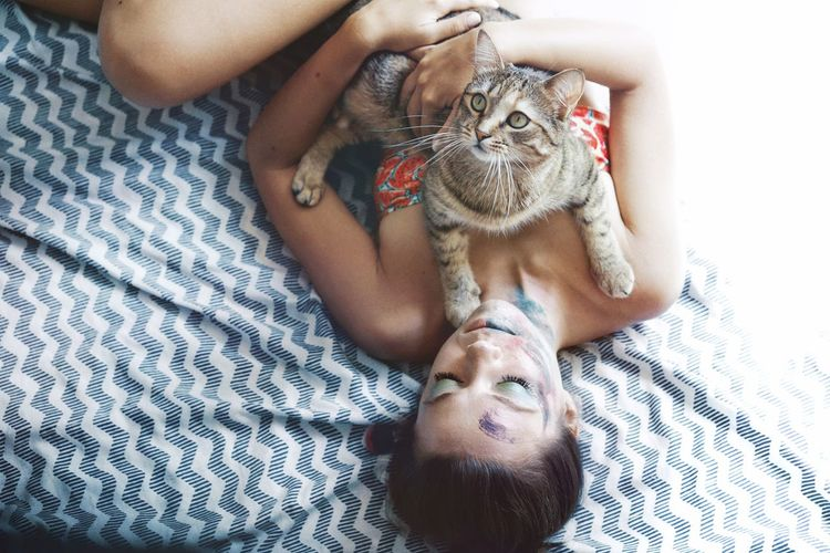 Woman lying with cat on bed at home