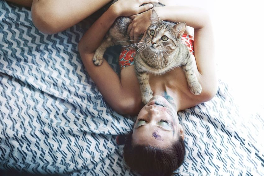 Pet Life  High Angle View Bonding Togetherness Cat Women Young Women Pets Portrait Domestic Cat Lying Down Relaxation Feline Bed Looking At Camera Bedroom Sitting At Home Lying Pampered Pets Home