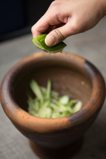 Close-up of hand squeezing lemon in bowl