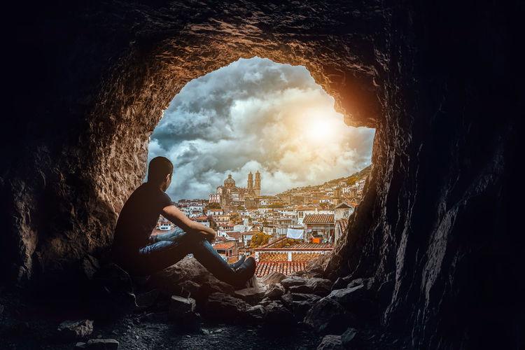 Man sitting on rock by buildings against sky