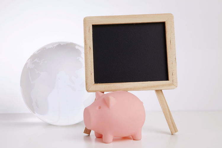 Close-up of blank blackboard and globe with piggy bank against white background