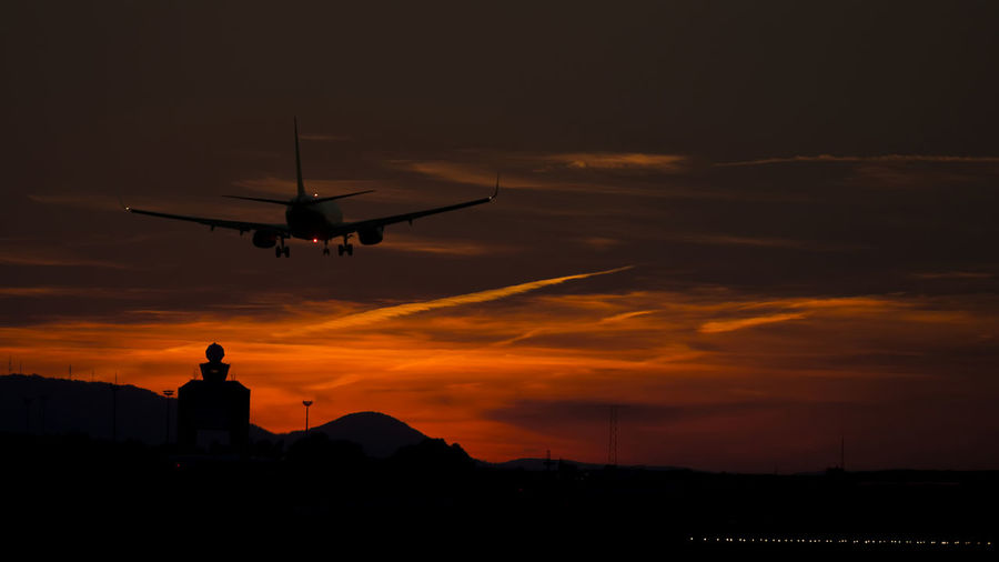 Silhouette airplane flying over control tower at budapest ferenc liszt international airport against sky