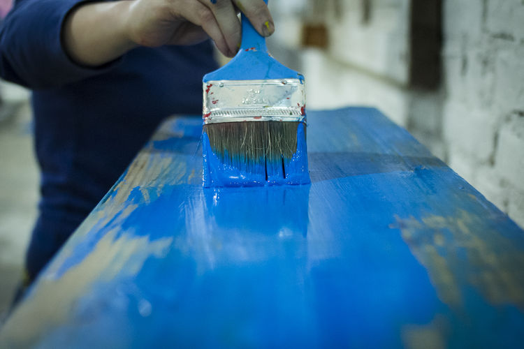 Midsection of painter painting wooden plank at workshop