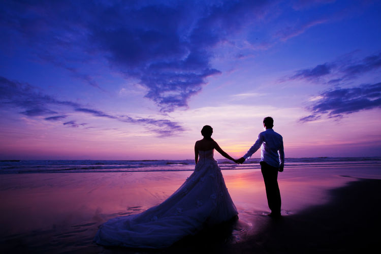 Bride And Groom Standing On Shore During Sunset