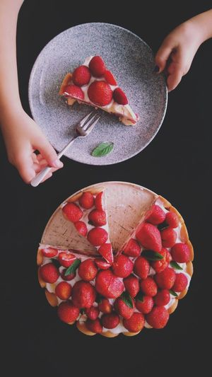 High angle view of person eating strawberry cake