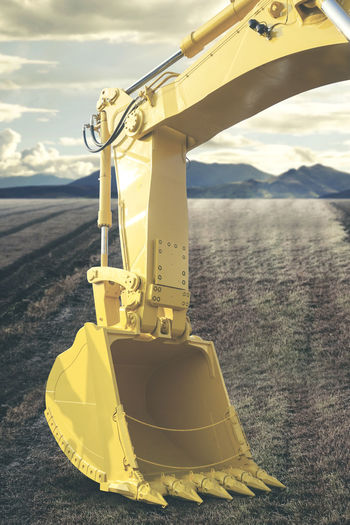Close-up of yellow construction machinery on field
