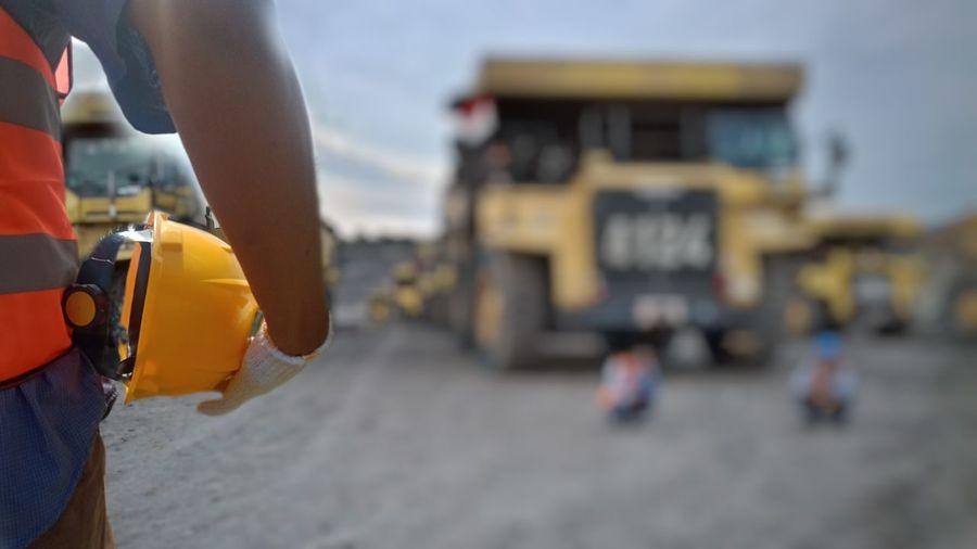 Close-up of hand holding yellow umbrella on beach
