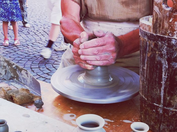 Midsection of man making pot at table