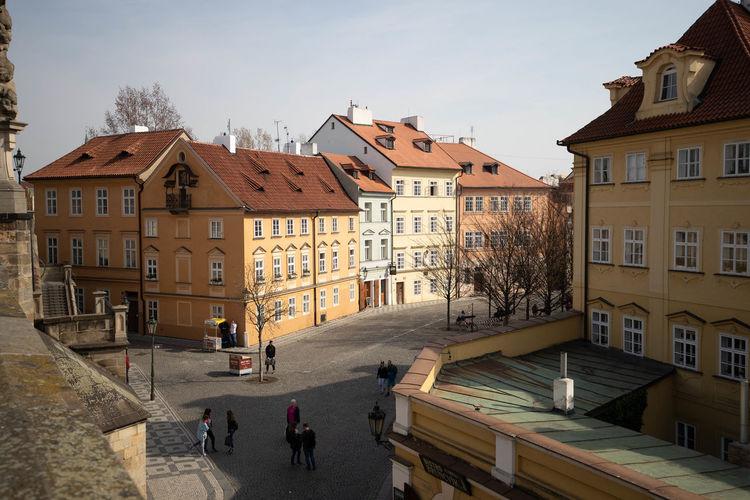 People walking on road amidst buildings in town