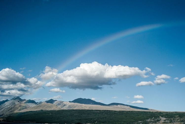 Scenic view of rainbow over landscape against blue sky