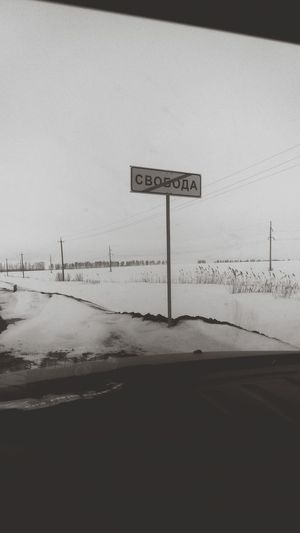 Road sign on snow covered land