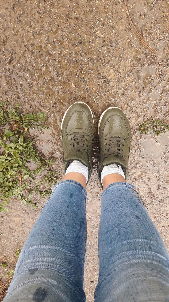 low section, shoe, human leg, one person, body part, personal perspective, human body part, jeans, real people, high angle view, casual clothing, standing, day, lifestyles, adult, women, directly above, outdoors, nature, human foot, human limb, flat shoe