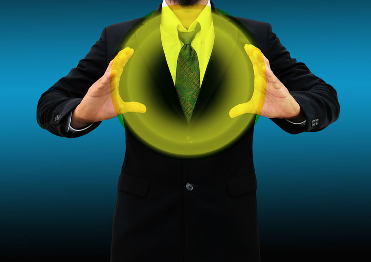 Digitally generated image of businessman holding yellow circle while standing against blue background