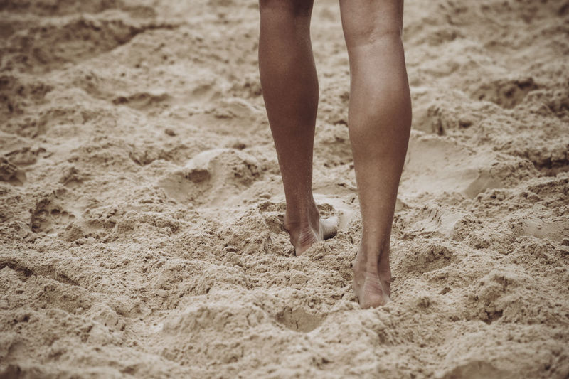 Low Section Of Person Walking On Sand