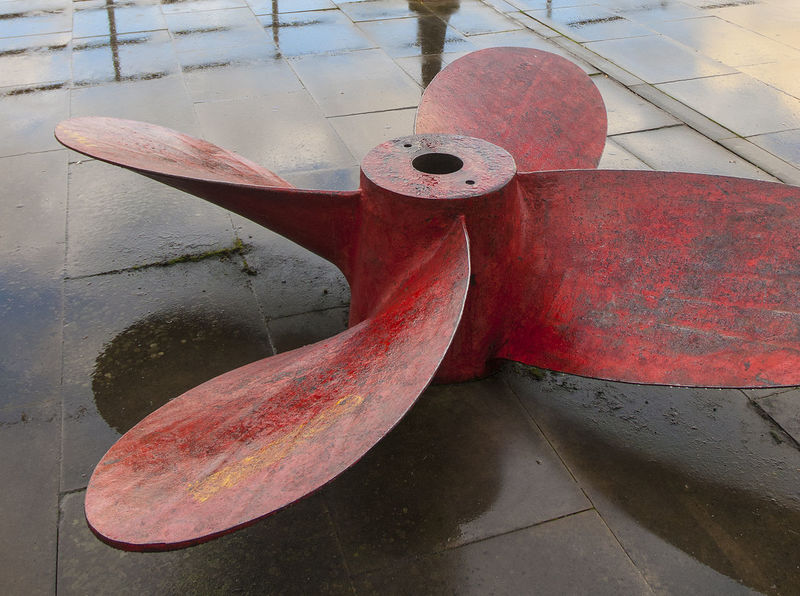 Propeller on a quay side, by the Thames. Day London No People No People, Outdoors Propeller Rain Soaked Red Ship Part Thames Water Reflections