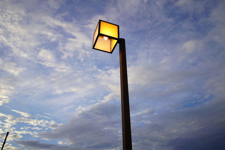 Low angle view of illuminated street light against cloudy sky