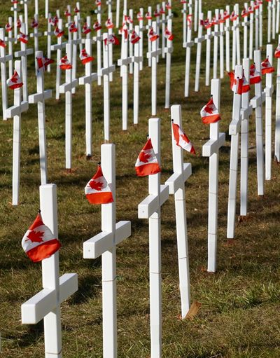 Field of white crosses with Canadian Flags on Remembrance Day Armistice Day Arrangement Canadian Flag Commemorate Crosses Day Field Grass In A Row Large Group Of Objects Memorial Memorial Day No People November 11th Outdoors Paying Respect Red Remembrance Day Respect Rows Of Crosses Rows Of Things Vertical Composition Veterans Memorial White Color White Crosses