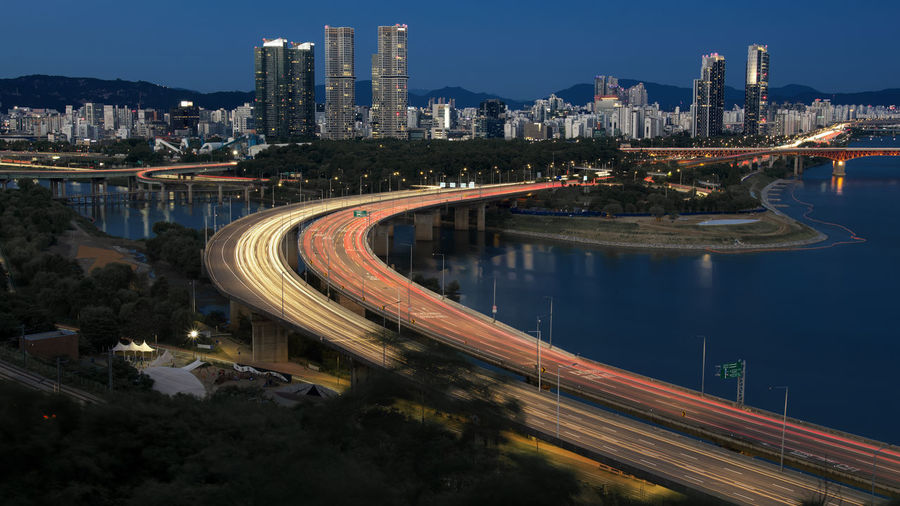 High angle view of light trails on road by buildings against sky at night