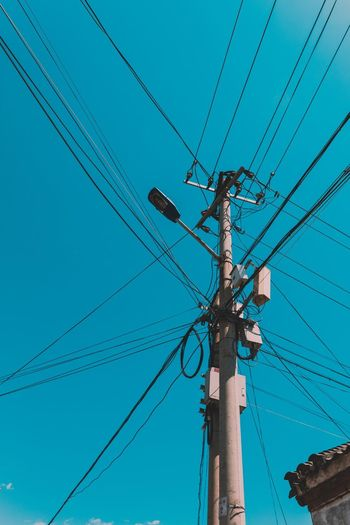 Cable Power Line  Power Supply Connection Electricity  Fuel And Power Generation Technology Low Angle View Electricity Pylon Pole Electrical Equipment Day Complexity Telephone Line Outdoors Communication No People Blue Sky Parallel