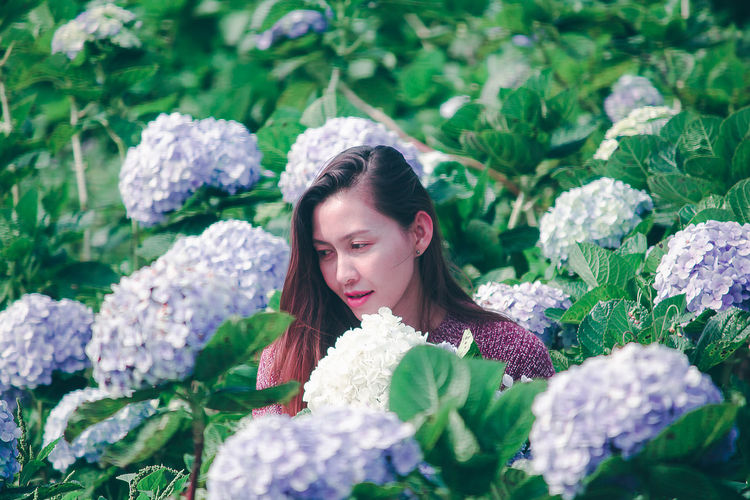 Smiling woman by flowering plants