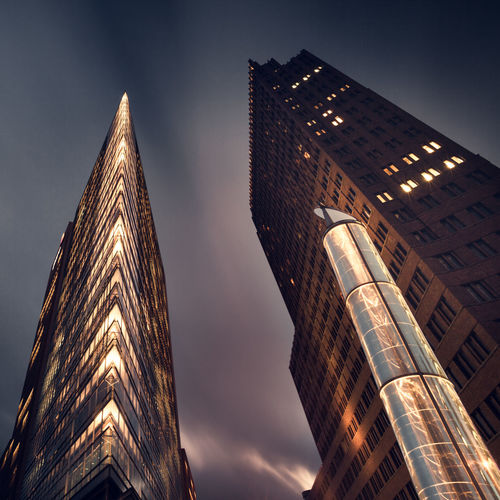 Low angle view of skyscrapers against sky at potsdamer platz in city during night