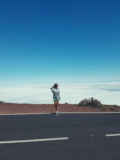 Full length of woman on road against blue sky