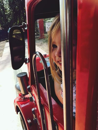 Close-Up Of Girl In Red Car