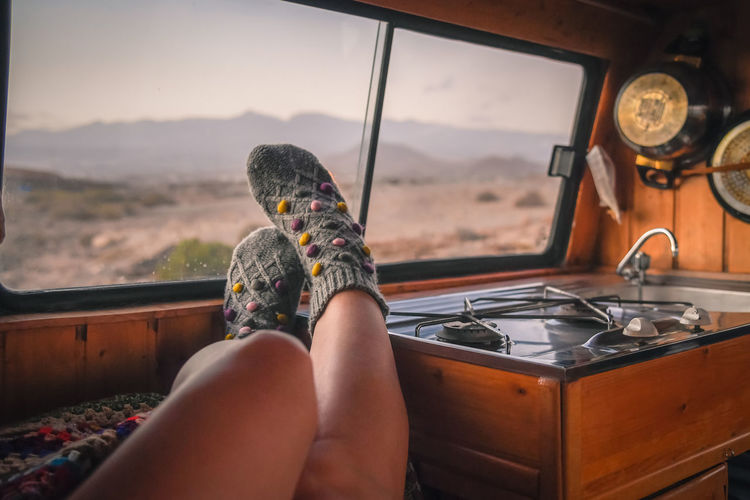 Woman feet in warm socks on vintage van. Mountain summer trip. Nomad life, girl legs in cute knitting sock near the window. Freedom travel concept. Autumn weekend. Female leg in an old wooden camper One Person Vehicle Interior Human Body Part Body Part Mode Of Transportation Transportation Real People Indoors  Adult Leisure Activity Low Section Window Glass - Material Relaxation Sitting Lifestyles Sky Nature Day Human Limb Road Trip