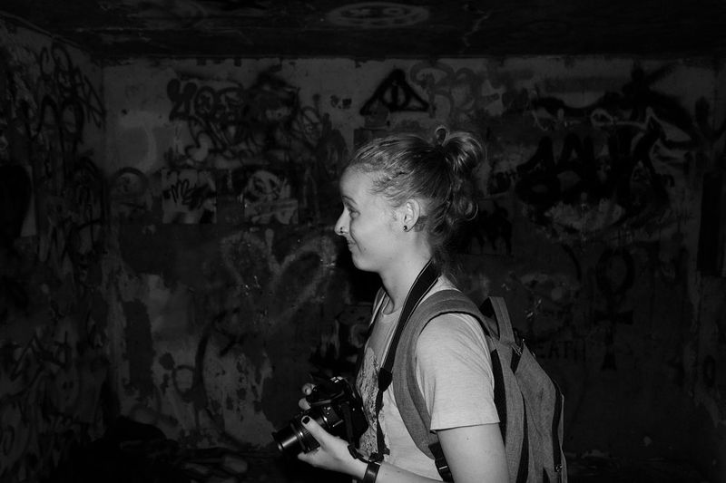 Side view of woman with camera by graffiti wall in abandoned room