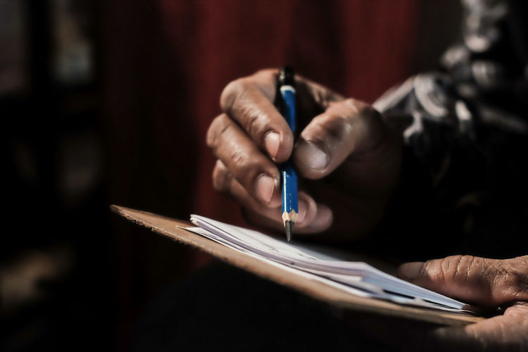 Close-up of man working in pen